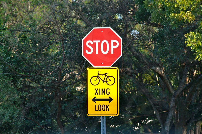 stop sign on top of xing look sign photo