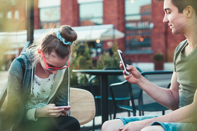 Couple of friends teenage girl and boy  having fun using smartphones sitting in center of town spending time together photo