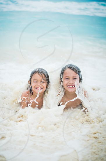 Two boys being splashed by a wave in the ocean.  photo
