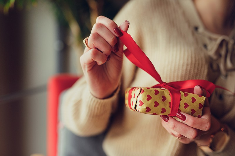 Pretty brunette woman sit on the flor and open her Christmas present with happy face near the window. - Image photo