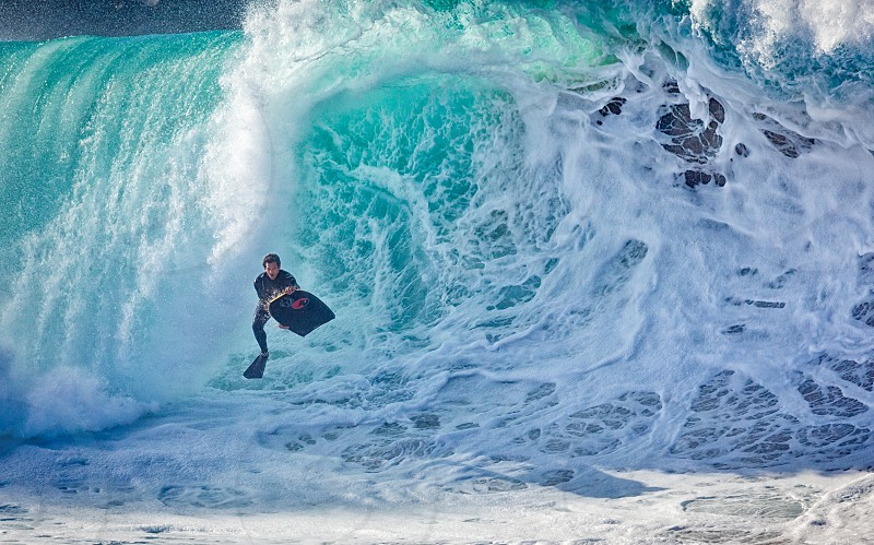 man surfing on blue sea during daytime photo
