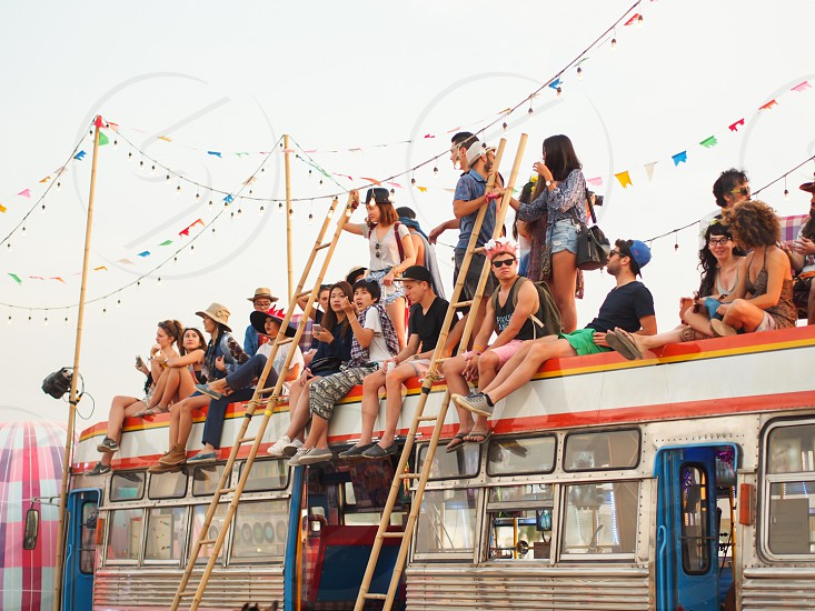 More people hanging out onto of a large bus at a festival. photo