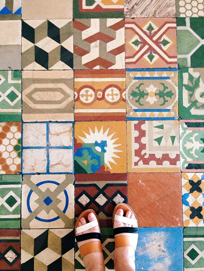 woman in sandals standing on multicolor patterned ceramic tiles photo