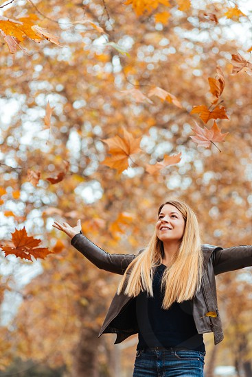 Young woman throwing yellow autumn leaves in the air photo