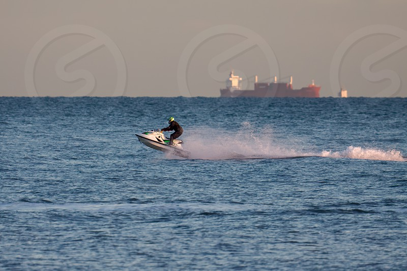 DUNGENESS KENT/UK - DECEMBER 17 : Man riding a jet ski off Dungeness beach in Kent on December 17 2008. One unidentified person photo