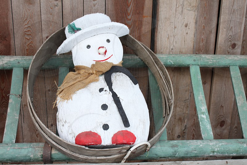 white snowman figurine on brown wooden surface photo