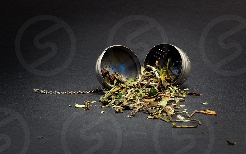 close photo of gray bowl with green dry leaf photo