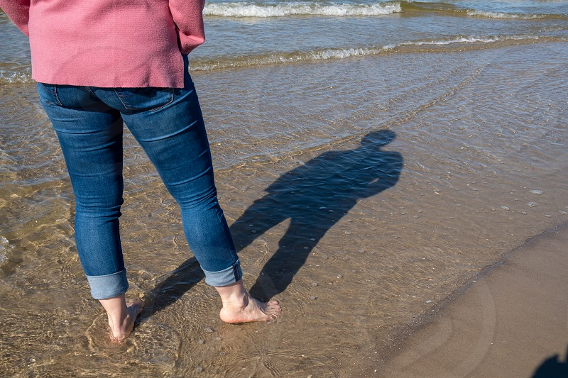 A woman barefoot with her shadow on the beach with waves of the Baltic Sea photo