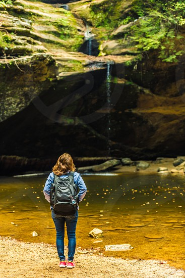 Female backpacker looking at waterfalls in Hocking Hills State Park in Logan Ohio. photo