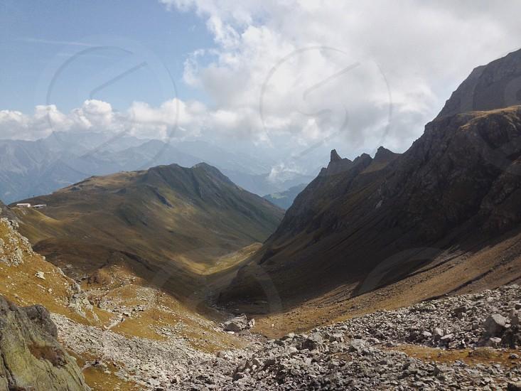 narrow pass between 2 hills under white cloudy sky photo