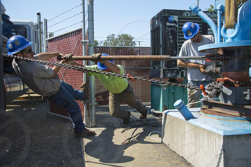 Tam Work - Men hard at work removing a well casing photo