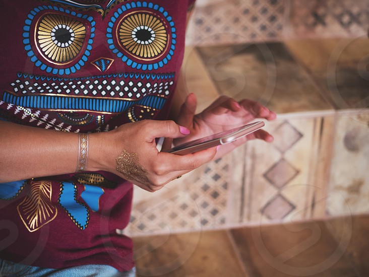 Woman with smartphone at home. Hands of young girl with flash tattoo using mobile device. photo