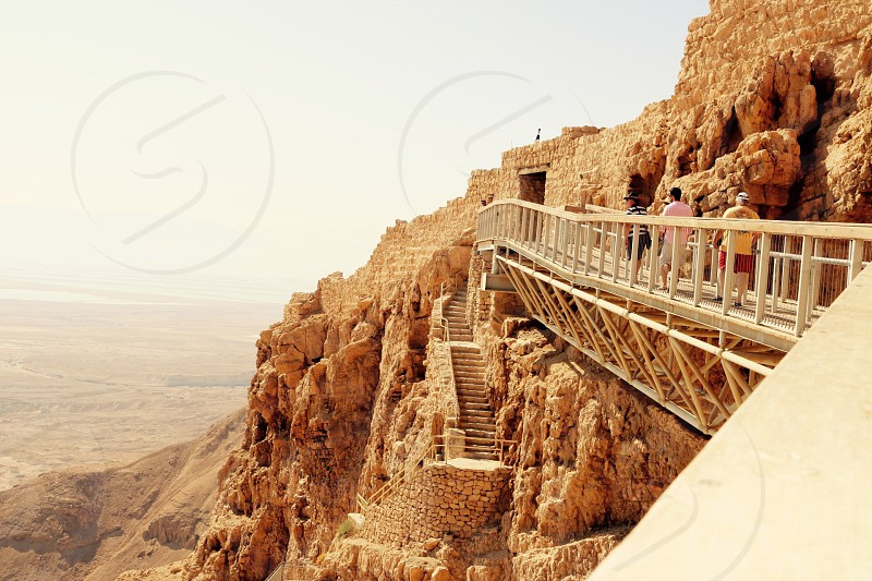 photography of person walking on walkway on cliff during daytime photo