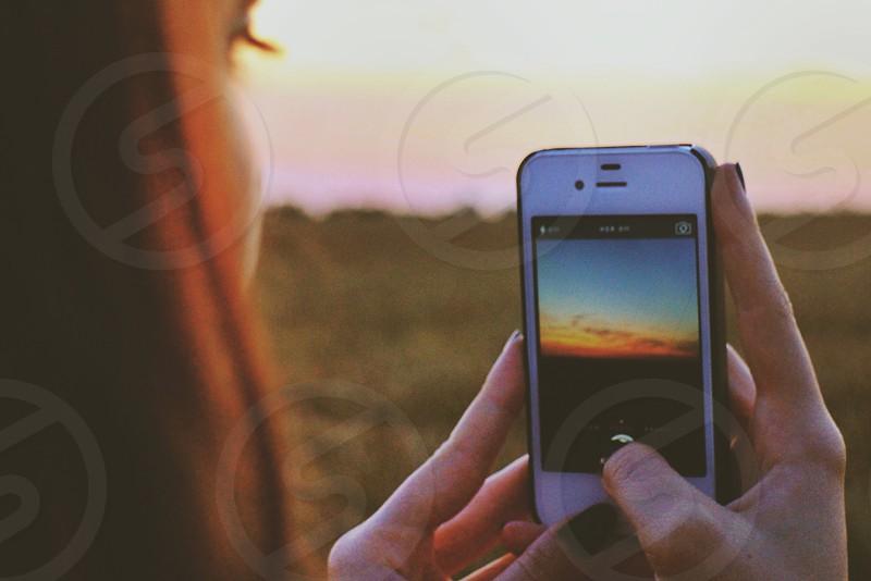 woman taking sunset photo on iphone photo