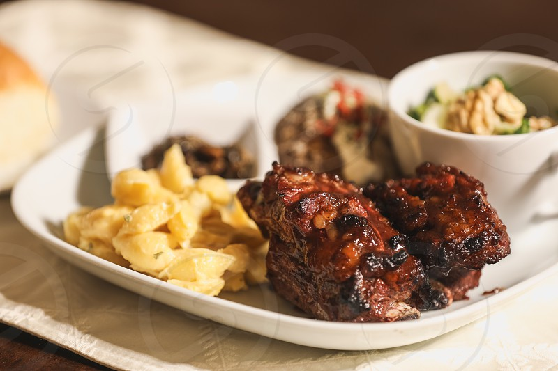 ribs dinner cooking dining home vegetables healthy homemade restaurant table mac and cheese pasta green colorful tasty food potato baked potato salad eating photo