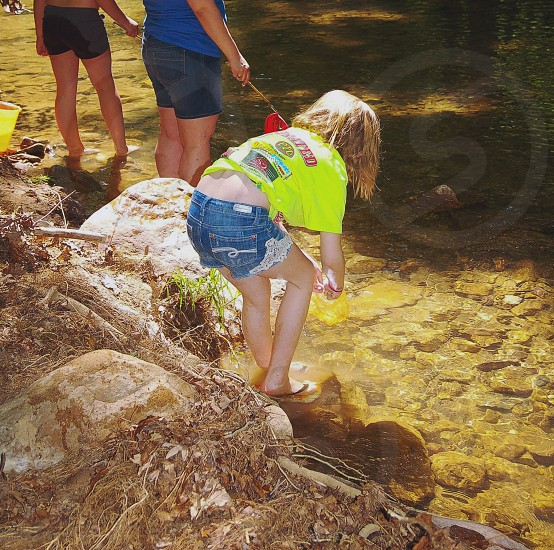 Child catching minnows in the creek photo