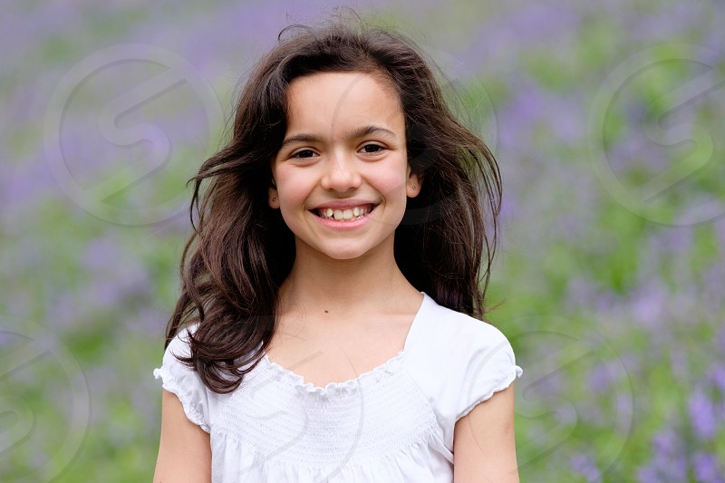 Portrait of a pretty dark long haired young ten year old girl wearing a white top with purple out of focus flowers behind her photo