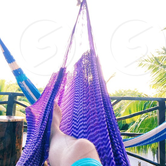 barefooted person in blue shorts lying on purple hammock on balcony under white sunny sky photo