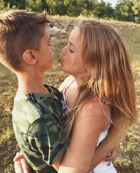 boy hugged girl and kiss boy on grass photo