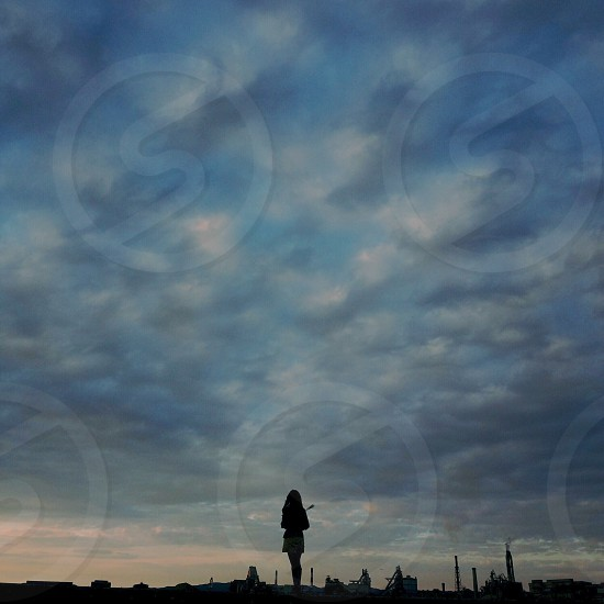 female standing over blue sky photo