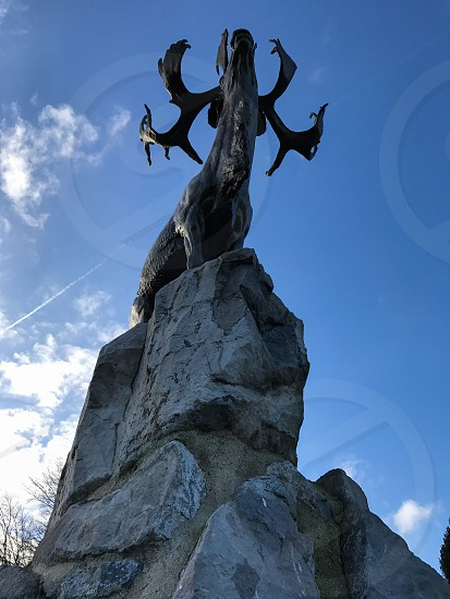 Outdoor day vertical portrait colour Beaumont Hamel France Somme western front Battle site battleground historic historical remembrance commemoration respect WWI WW1 World War One First World War Memorial blue sky War warfare battle Caribou Statue monument crescent moon metal Newfoundland forces army Canada photo