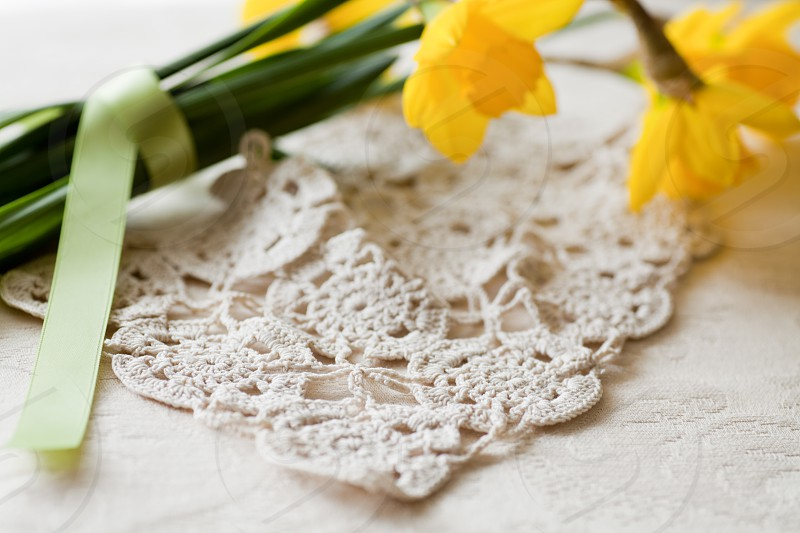 Easter decor ~ Yellow Daffodil flowers on lacy crochet doily indoors daylight setting. photo