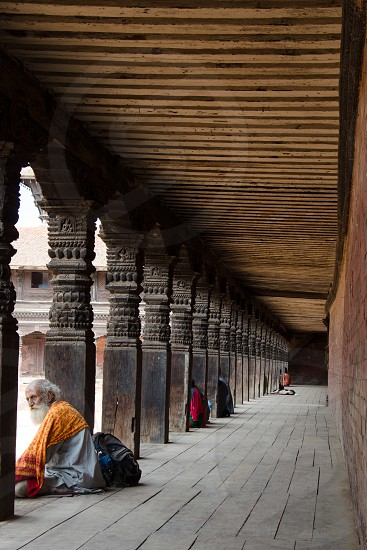A man relaxes in the archways of a historical building in Bhaktapur Nepal photo