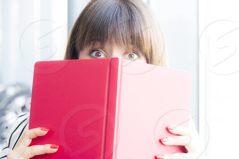 Woman peeking behind her notebook in her home office photo