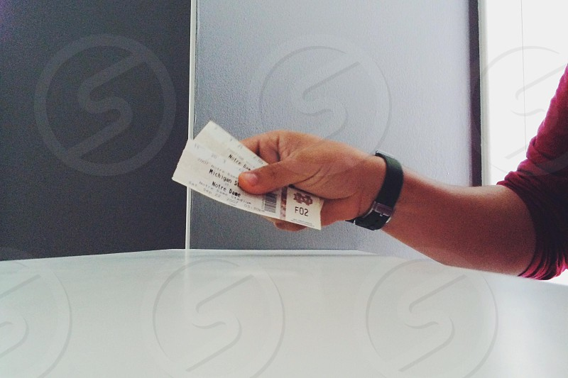 person holding a white ticket photo