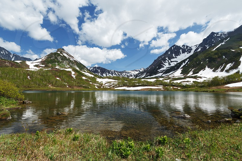 Summer landscape of Kamchatka: beautiful view of Mountain Range Vachkazhets mountain lake and clouds in blue sky on sunny day. Eurasia Russia Far East Kamchatka Peninsula. photo