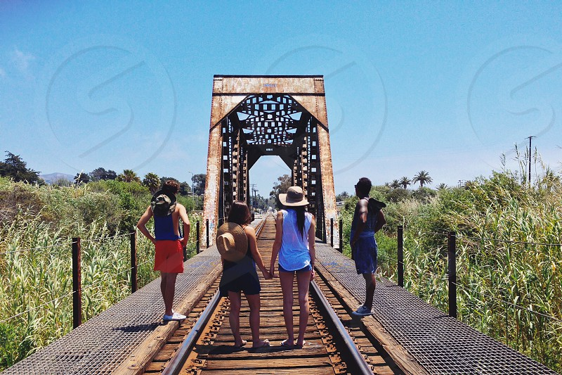 woman in white tank top holding hands with woman in black shorts standing beside 2 men on railroad photo