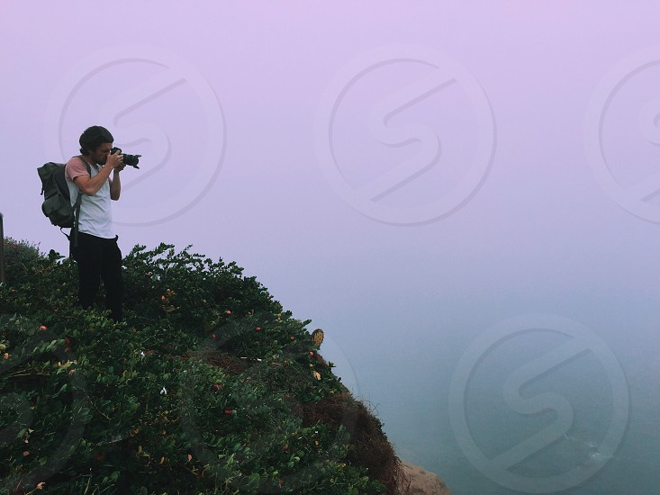 person carrying backpack standing on grassy cliff capturing photo of body of water during sunset photo