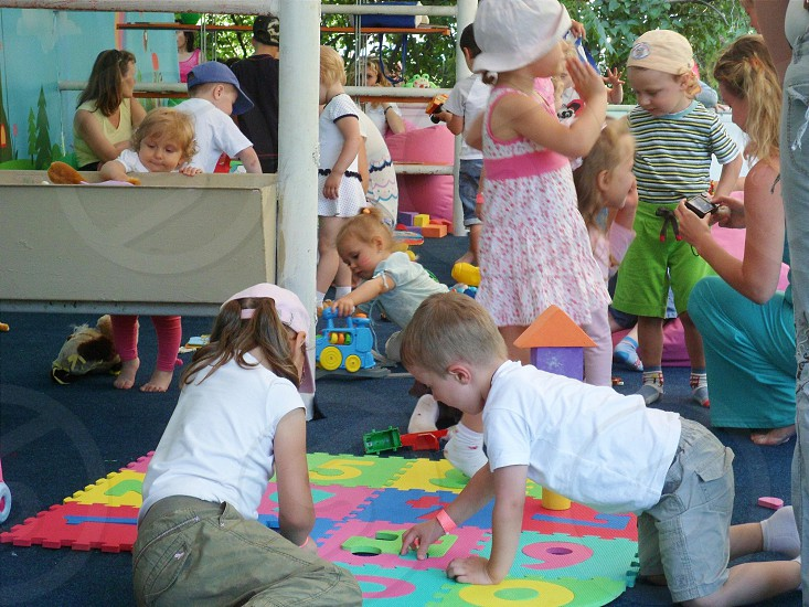 boy on white crew neck shirt near girl wearing pink baseball cap playing Number Puzzle mat photo