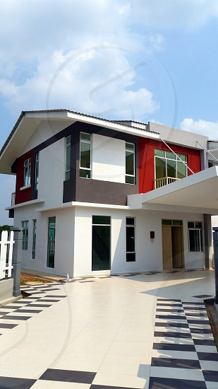 white black red painted concrete two storey house under white blue sky during daytime photo