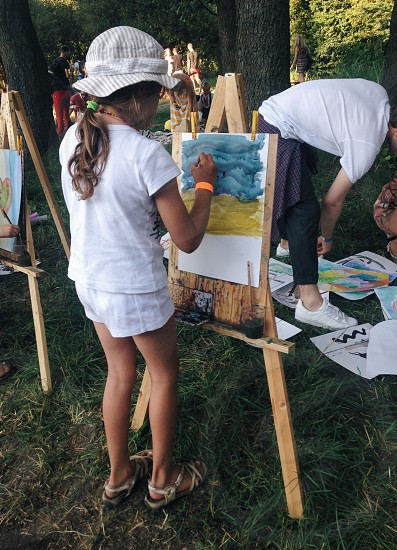little girl in summer clothes and hat painting on a canvas attached to an easel with others doing the same under trees photo