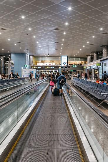 Passengers on mechanical walkway in the airport of Madrid. Interior shot photo