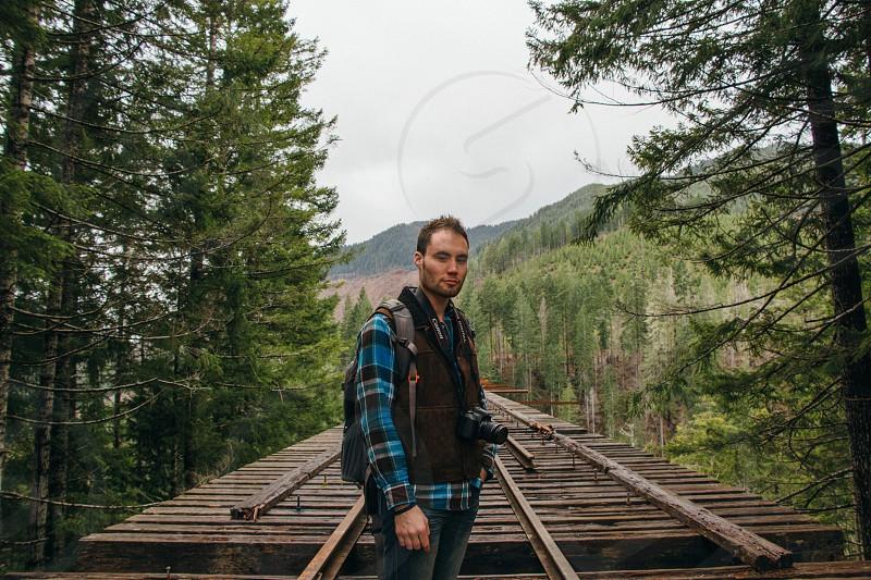 man standing at the wooden bridge photo