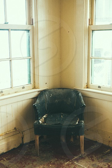 green upholstered wooden chair in empty corner photo