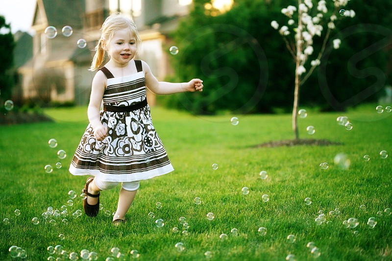 girl running in bubbles on lawn photo