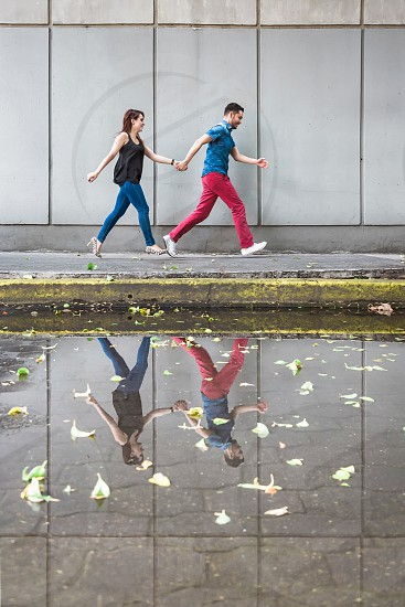 a young couple run across a pavement with their reflection in a puddle on the ground photo