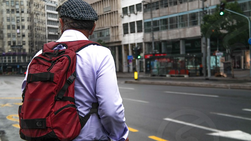 man in white long sleeved shirt with red backpack photo