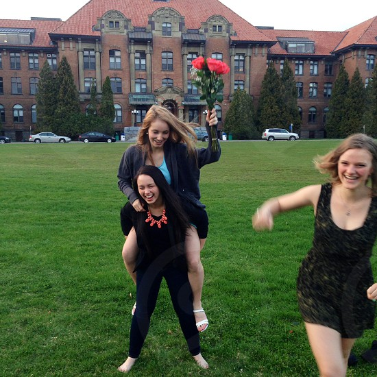 A group of girls who are friends having fun at school and giving piggy back rides at a graduation art show in the West Island of Montreal at John Abbott College. photo