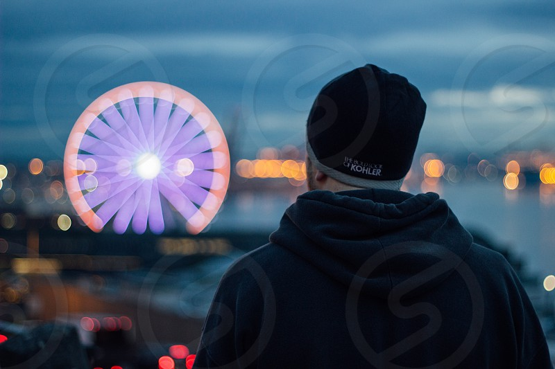 a man looking out to a ferris wheel on the puget sound in Seattle photo