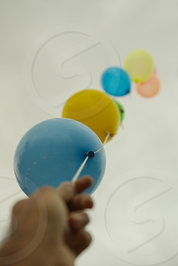 man hand holding balloons colorful overcast sky up reflection of Christmas lights yarn attached photo
