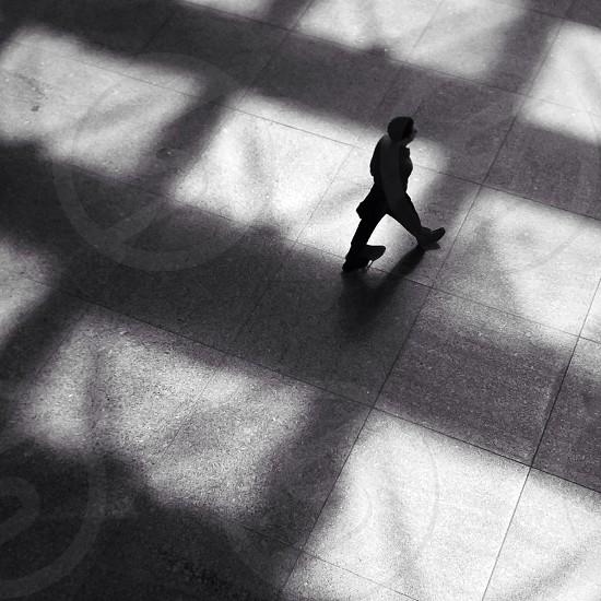 man walking on grey floor tiles photo