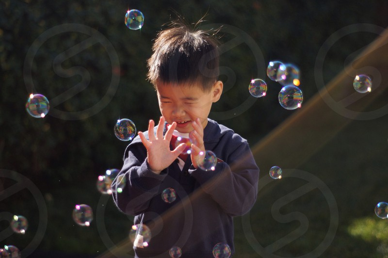 boy in blue jacket playing with bubbles in open field photo