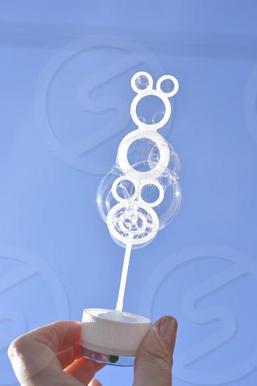 white plastic bubble wand with bubbles photo