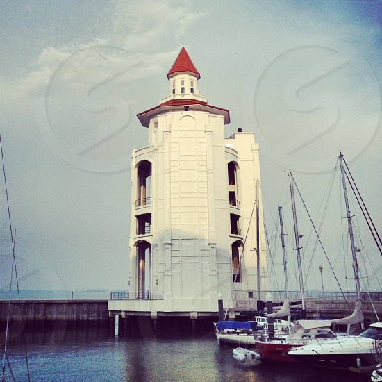 white painted building surrounded by body of water with sailboats taken under white clouds during daytime photo