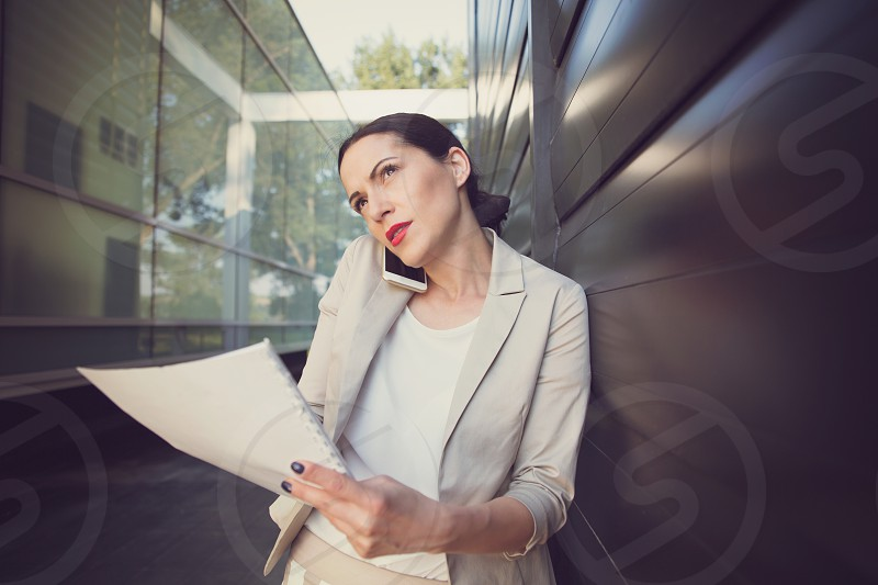 Business woman on the phone holding papers at office building photo