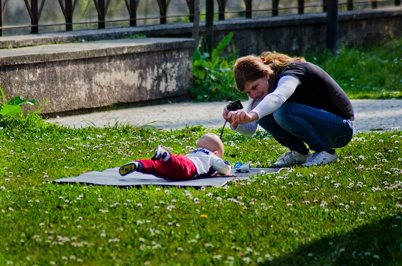 woman taking pictures of a baby lying on a blue mat photo